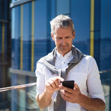 man using smartphone near modern bright business center exterior