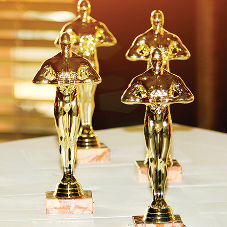 oscar-looking statues sitting on a table in a room