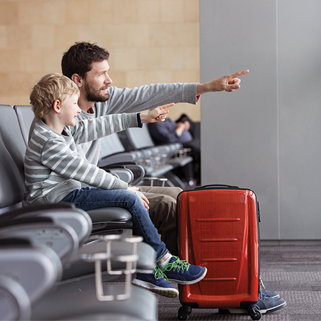 positive smiling boy and his father waiting at the airport for plane departure