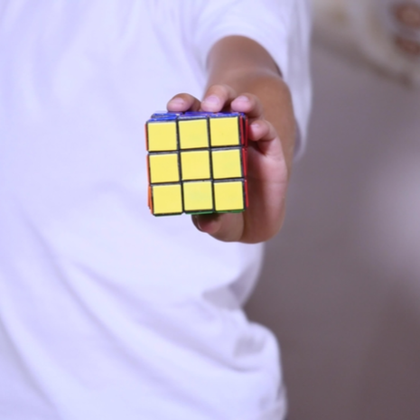 the boy is sitting on the couch and collects a rubic's cube