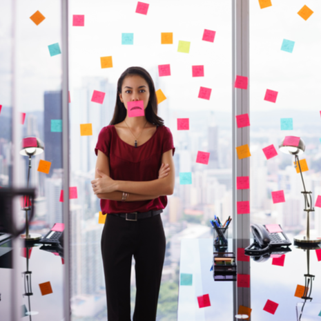 woman working in modern office with reminders on skyscraper window