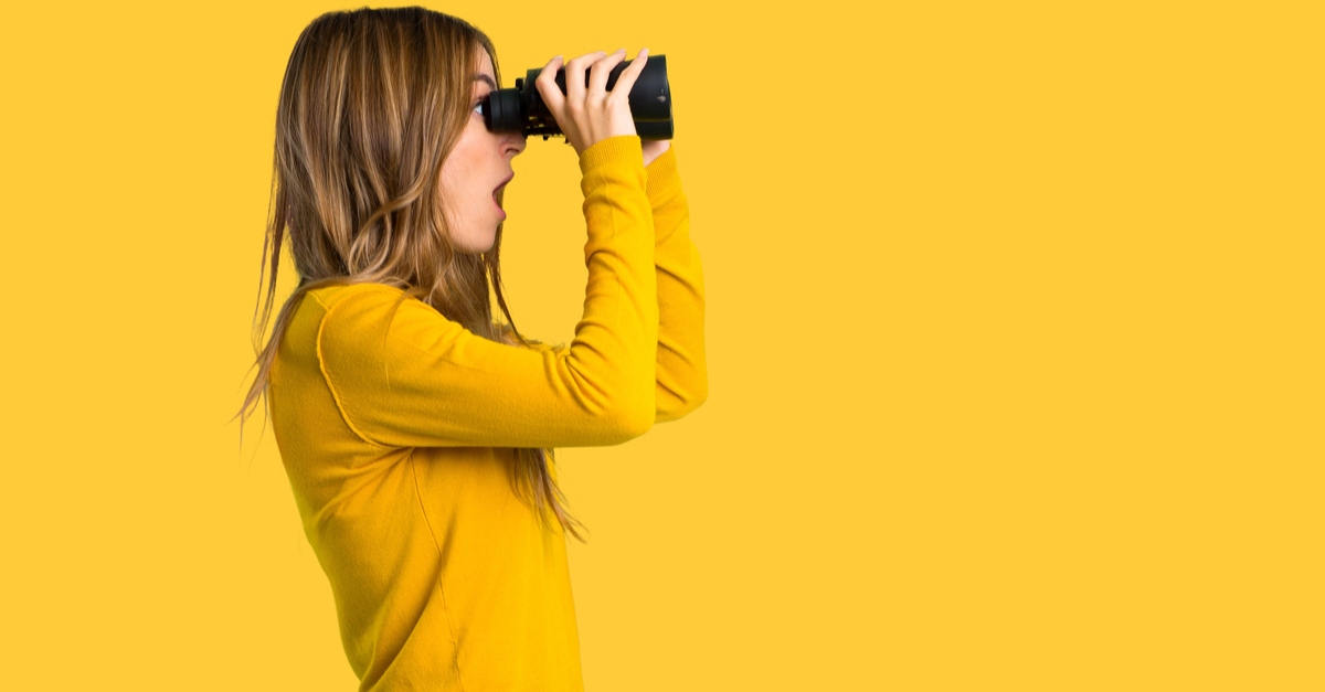 young girl with yellow sweater and looking in the distance with binoculars on isolated yellow background-SM