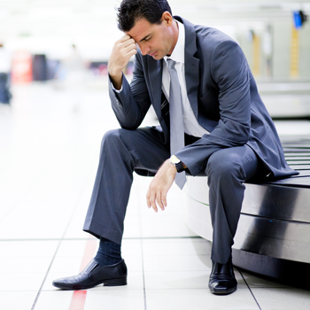 businessman-sitting-on-baggage-claim-conveyor-in-airport