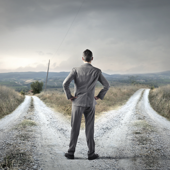 businessman-standing-at-fork-in-dirt-road