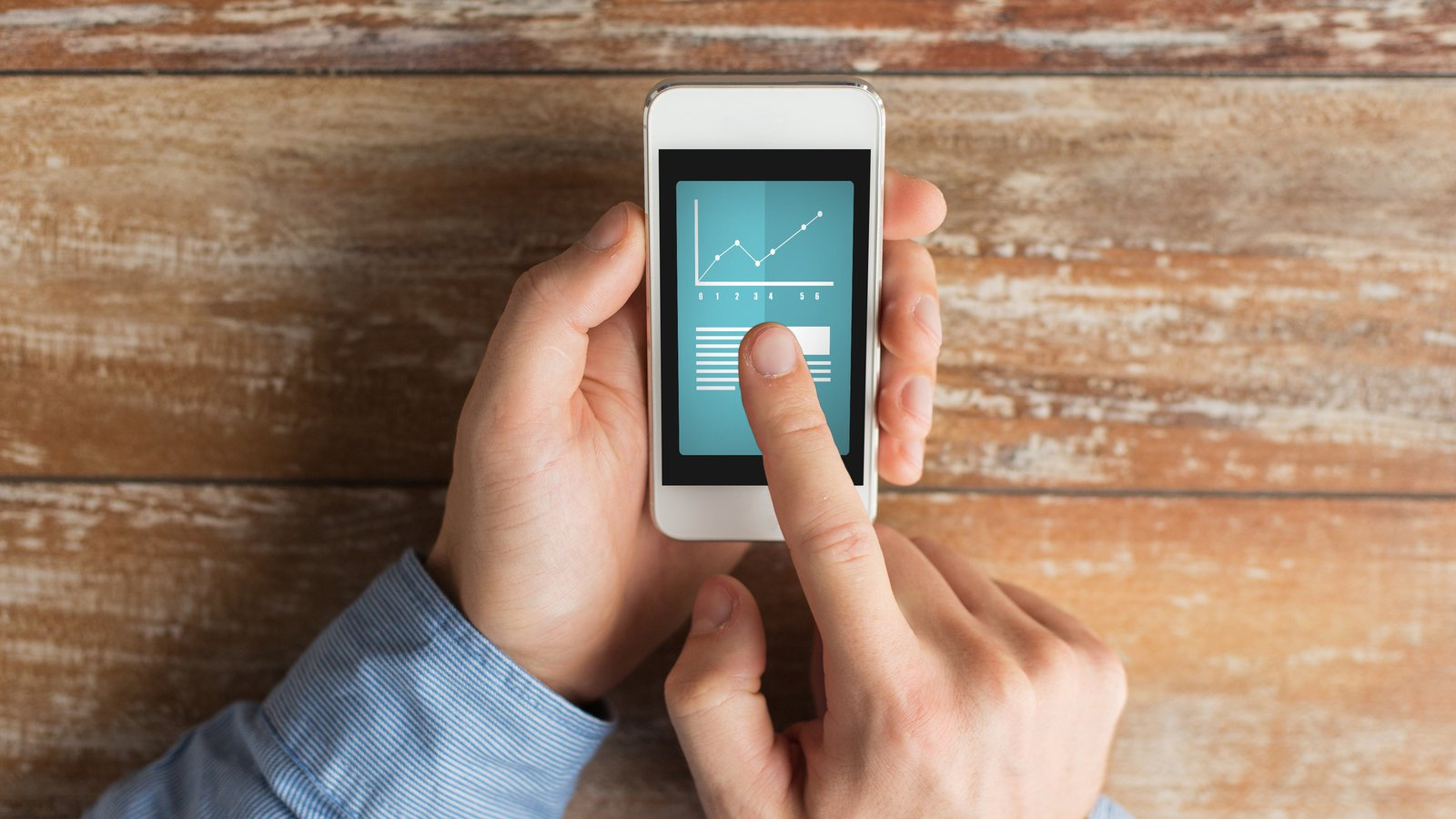 close up of male hands holding smartphone and pointing finger to graph feature