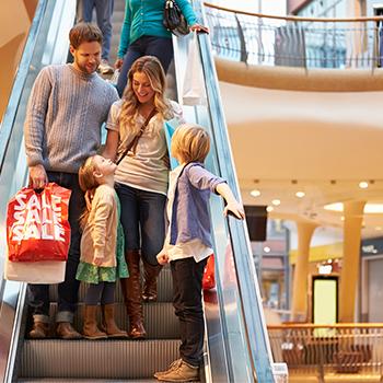 family riding mall escalator