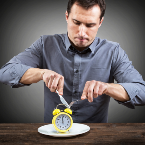 man cutting clock sitting on plate