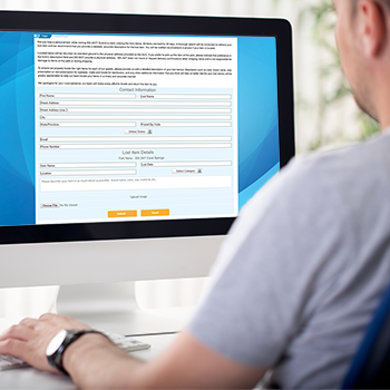 man sitting in front of computer with lost and found software web form