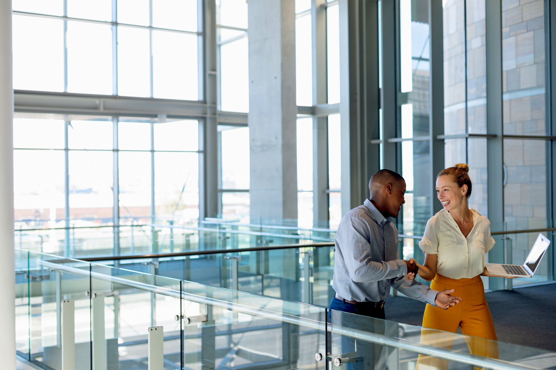 Businessman shaking hand of businesswoman in building terminal