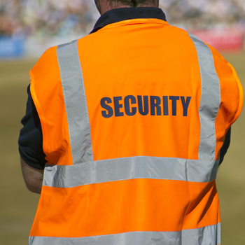 stadium-security-staff-facing-blurred-field-background-with-the-word-security-on-jacket